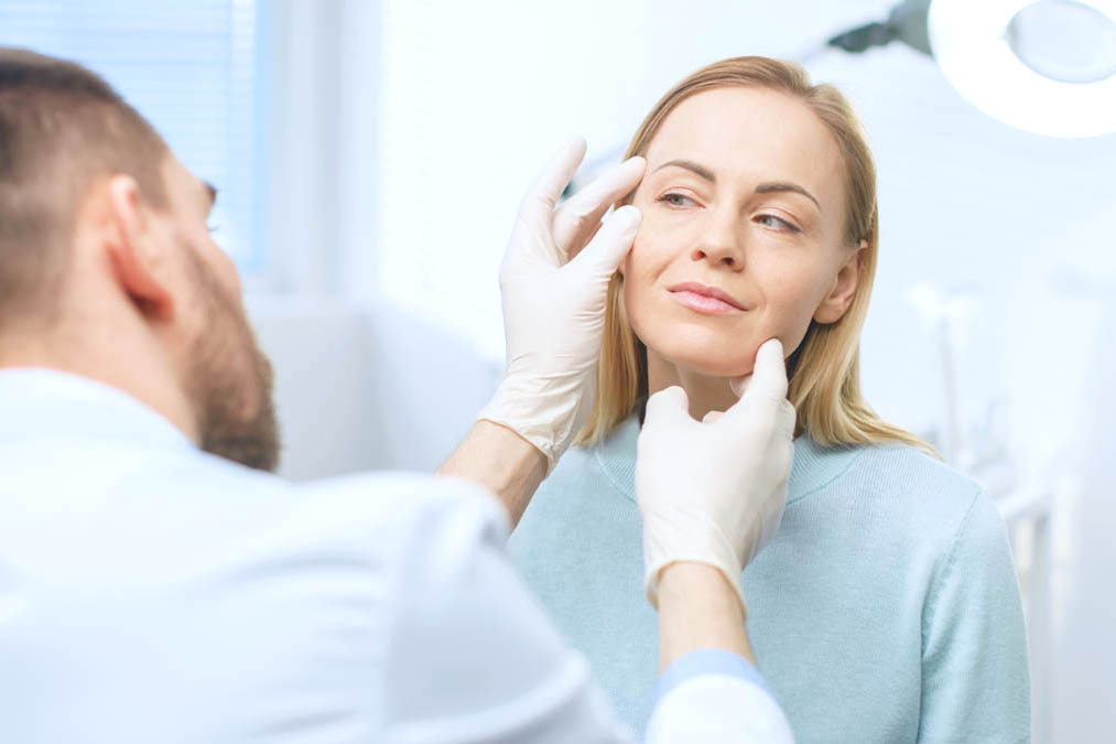 Doctor examining woman's face